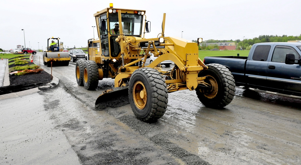 ROUGH ROAD: Motorists drive around a grader and roller on Waterville Commons Drive Monday as the road is repaved. Poor conditions and lots of traffic Saturday contributed to major traffic congestion, and city officials said they fear it can happen again.