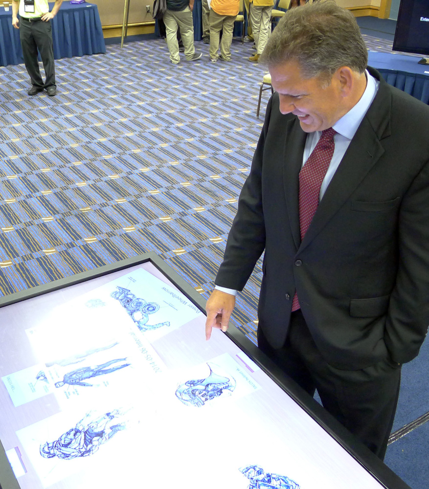 James Geurts, deputy for acquisition of the U.S. Special Operations Command at MacDill Airforce Base, looks at sketches of the Tactical Assault Light Operator Suit during the Special Operations Forces Industry Conference in Tampa, Fla., on Monday.