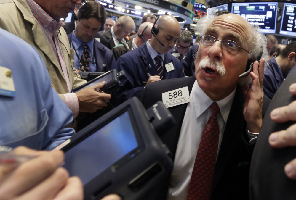 Trader Peter Tuchman, right, works on the floor of the New York Stock Exchange on Friday.
