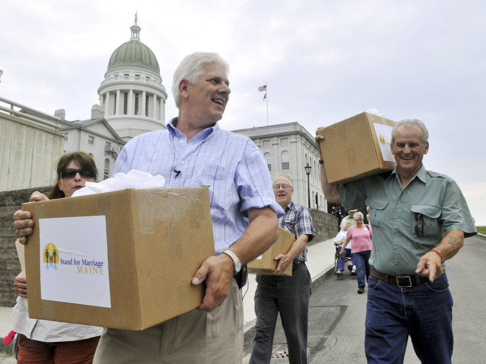 """Bob Emrich, left, is shown delivering signatures collected by Stand for Marriage Maine to the secretary of state. Emrich, who helped run the 2009 and 2012 ballot committees that National Organization for Marriage dollars helped fund, said those donors should be protected. """"People are targeted for harassment for contributing to a cause they believe in,"""" he said."""