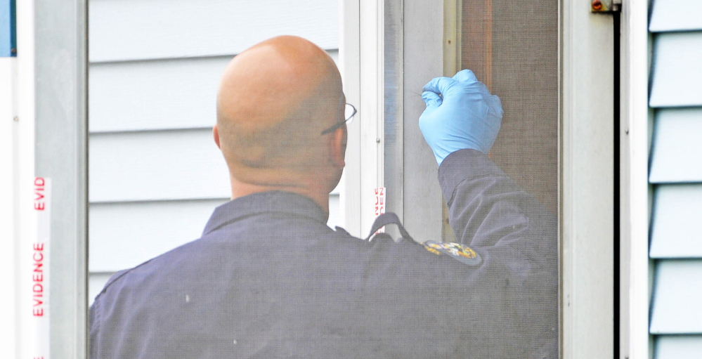 EVIDENCE: An investigator with the Maine State Police Major Crimes Unit examines a door at the back entrance to the residence of Aurele Fecteau, 92, who was found dead in his home on Brooklyn Street in Waterville on Friday.