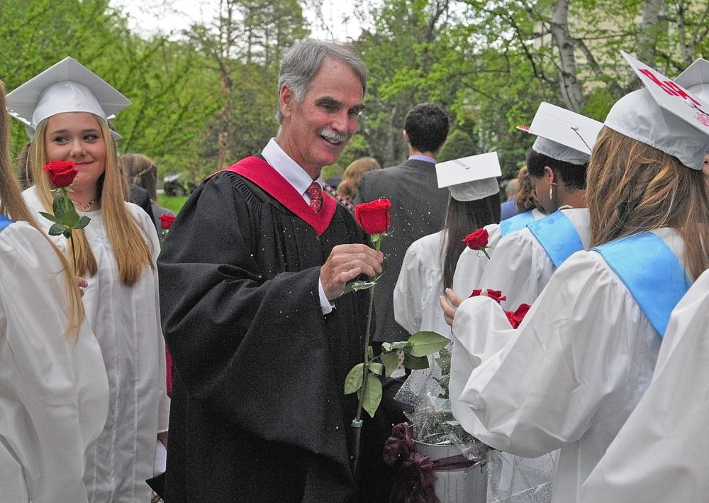 THE FLOWER HOUR: Head of School Pat McInerney shakes water off a rose as he hands it to one of the female graduates before they file into graduation ceremony Saturday at Kents Hill School in Readfield.
