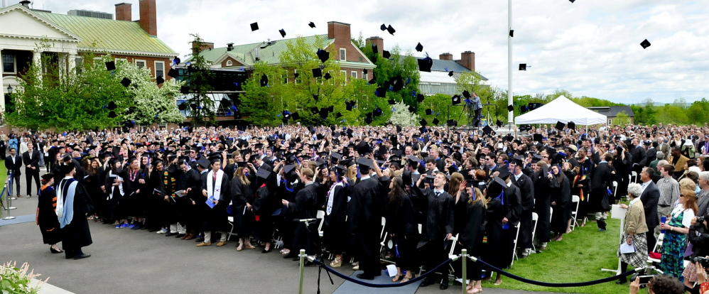 UP AND AWAY: The Colby College graduating class signals the end of their commencement by tossing their mortarboard caps into the air in Waterville on Sunday.
