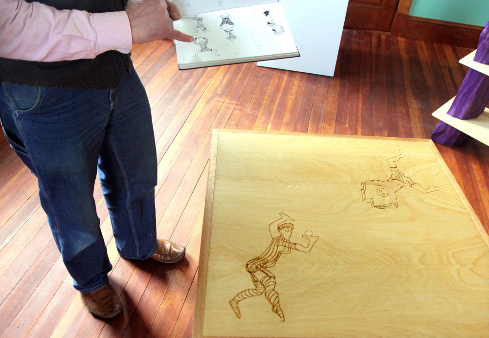 BEFORE AND AFTER: Dutch woodworker Erik Groenhout shows a sketch book he used to create a weave table on display in his gallery at the old Oddfellows Hall in Mt. Vernon on Sunday. Groenhout has slowly been restoring the building since acquiring it in 2011.