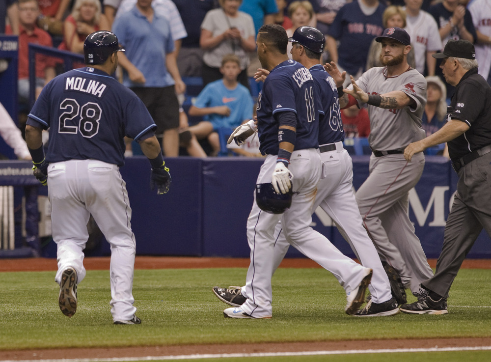Red Sox left fielder Jonny Gomes, second right, rushes past umpire Larry Vanover, right, toward Tampa Bay' Jose Molina (28), Yunel Escobar (11), and third-base coach Tom Foley (66) at the start of a benches-clearing incident in the seventh inning Sunday.