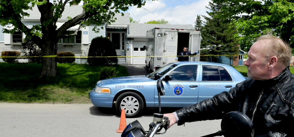 ACTIVE INVESTIGATION: Paul Fecteau watches as a Maine State Police detective exits a Maine State Police Major Crime Unit vehicle outside the cordoned off home of his father Aurele Fecteau's home in Waterville on Sunday. Aurele Fecteau was found dead by his elder brother Ernest last Friday, according to Paul Fecteau. The death was ruled a homicide on Sunday.