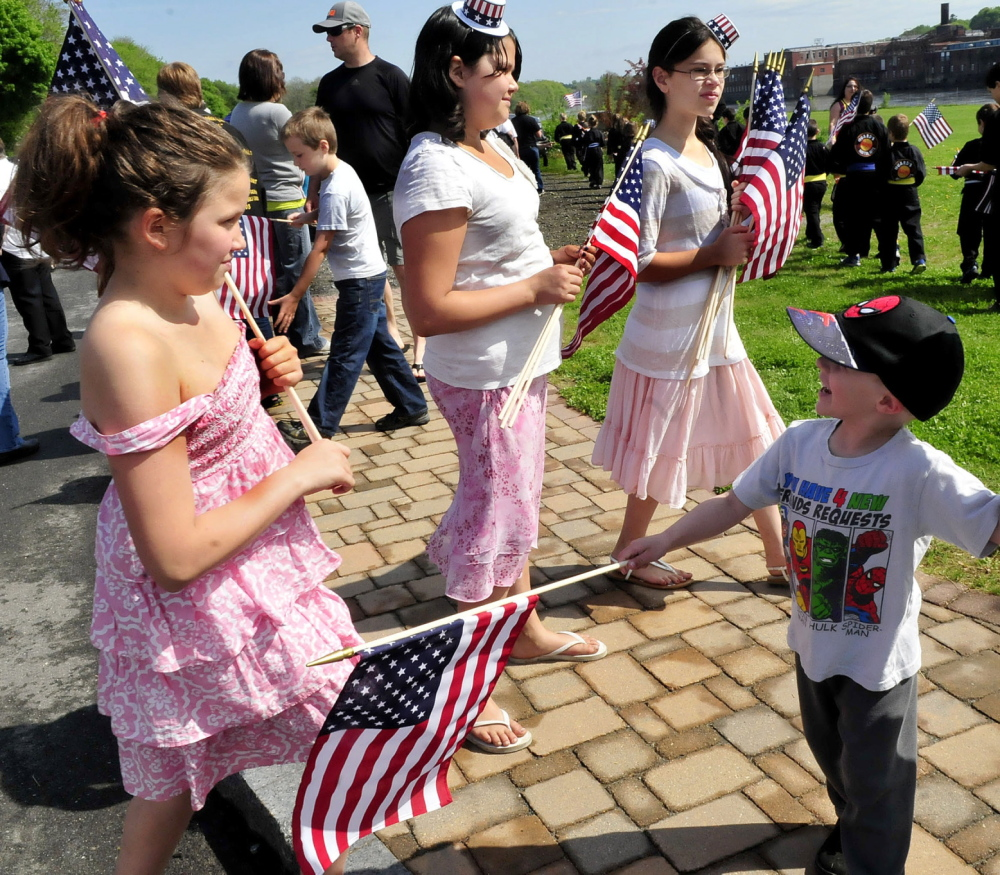 Staff photo by David Leaming YOUNG PATRIOTS: These girls handed out American flags to parade marchers including Cody St. Pierre prior to the Memorial Day parade in Waterville on Monday, May 26, 2014. From left are Kaylee Levesque and sisters Aubrey and Raygen.