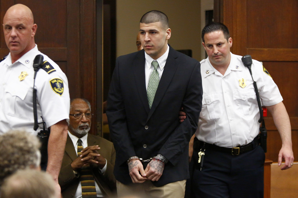 Former New England Patriots tight end Aaron Hernandez is led into the courtroom to be arraigned on homicide charges at Suffolk Superior Court in Boston on Wednesday. Hernandez pleaded not guilty in the shooting deaths of Daniel de Abreu and Safiro Furtado.