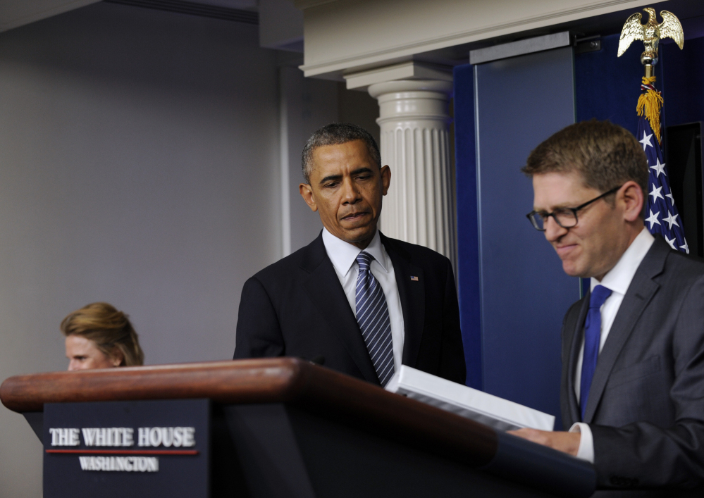 White House press secretary Jay Carney closes his briefing book as President Barack Obama makes a surprise appearance to the Brady Press Briefing Room of the White House in Washington on Friday to announce that Carney will be stepping down in June.