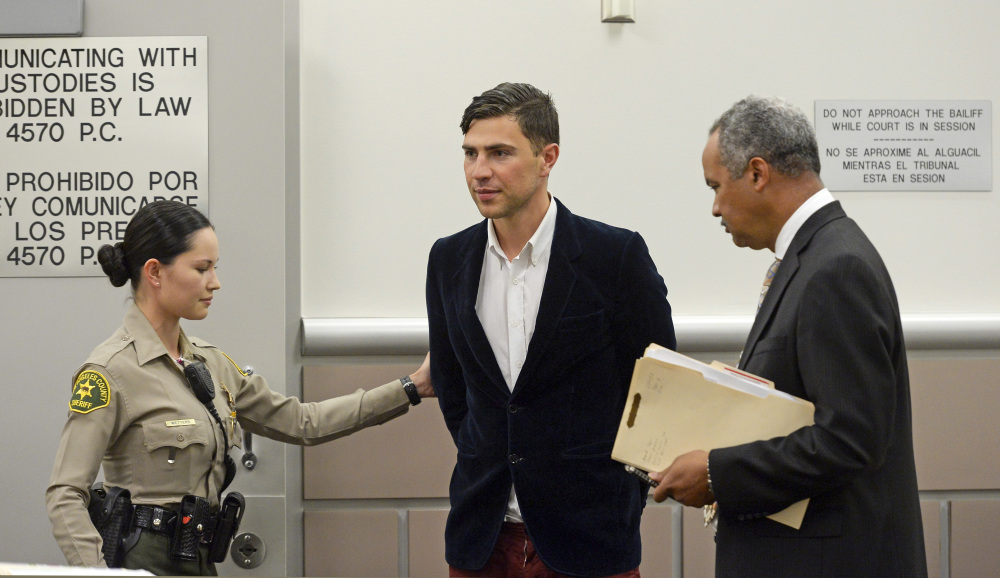 Vitalii Sediuk, from Ukraine, is led into the courtroom with his attorney Anthony Willoughby, right in Los Angeles Superior Court Friday, May 30, 2014, in Los Angeles. Sediuk faces four misdemeanor charges in connection with an alleged May 28 attack on actor Brad Pitt at a Los Angeles movie premiere.