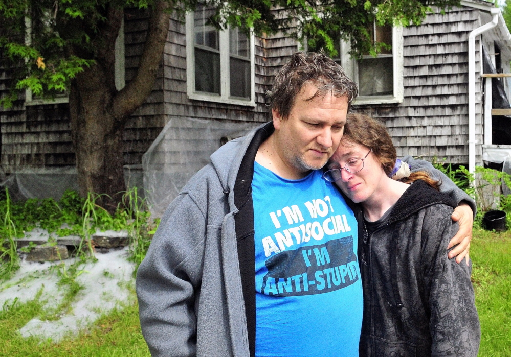 Home Lost: Patrick Lunt, left, hugs his wife, Beth Lunt, after an early morning fire on Saturday heavily damaged their home at 4 Pine Knoll Road in Winthrop. Patrick Lunt called her a hero for noticing the fire and waking him, their 19-year-old son, Storme, and another man and getting them out of the house.