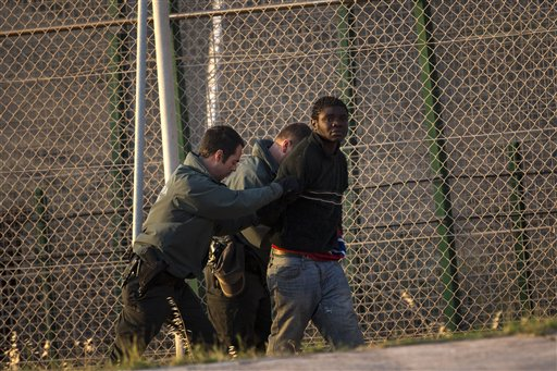 A sub-Saharan migrant is detained by Spanish guards after scaling a fence that divides Morocco and the Spanish enclave of Melilla early Wednesday morning.