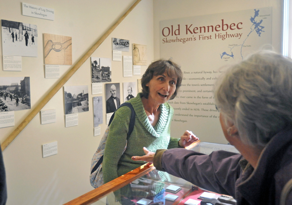 """LOG DRIVE HISTORY: Maureen Calder, center, takes in the exhibit of The Skowhegan History House Museum & Research Center's exhibit """"Old Kennebec - Skowhegan's First Highway"""" on Wednesday."""