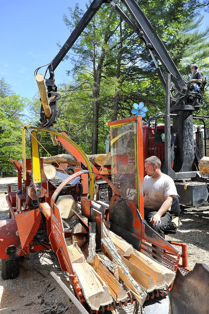 Mark Killinger, back, owner of Atlantic Firewood, adds hardwood logs to the line as his son, Mike Killinger, owner of Maine Logging, tends the cutting and processing machine as they work together to cut and process firewood.