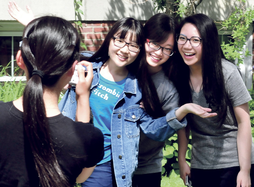 GRADUATE SMILES: Maine Central Institute students pose for photos following commencement exercises in Pittsfield on Sunday. Diyun Wang, left, photographs graduates, from left, Yiyi Fei, valedictorian Lijia Chen and salutatorian Xinxiu Zhong. The three seniors headed to Boston where they will fly to China on Monday.