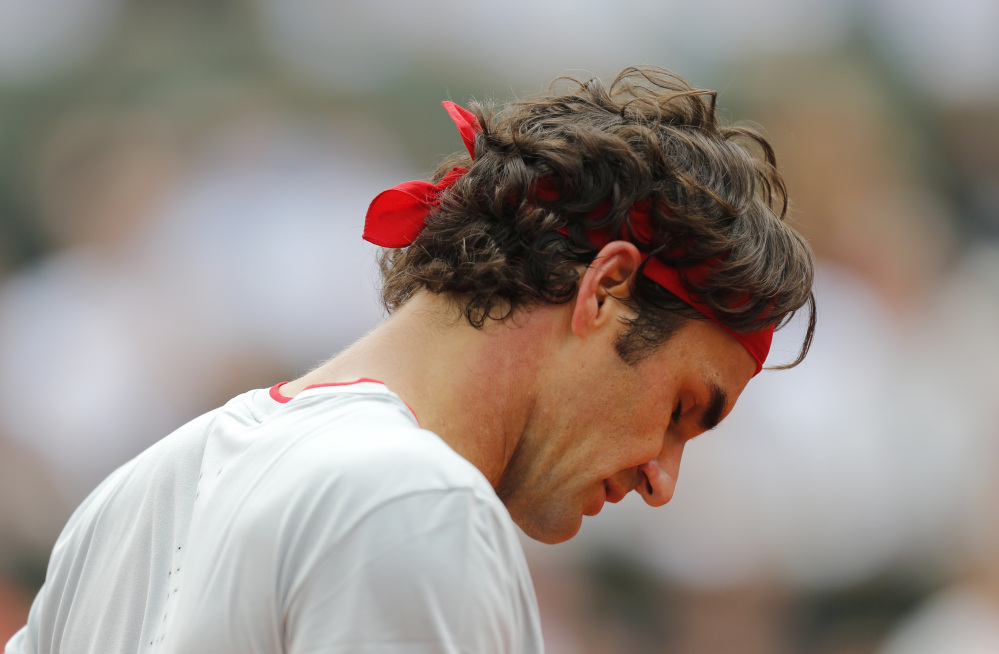 Roger Federer looks down as he plays Ernests Gulbis in the fourth round at the French Open on Sunday. Federer lost, 6-7 (5), 7-6 (3), 6-2, 4-6, 6-3.