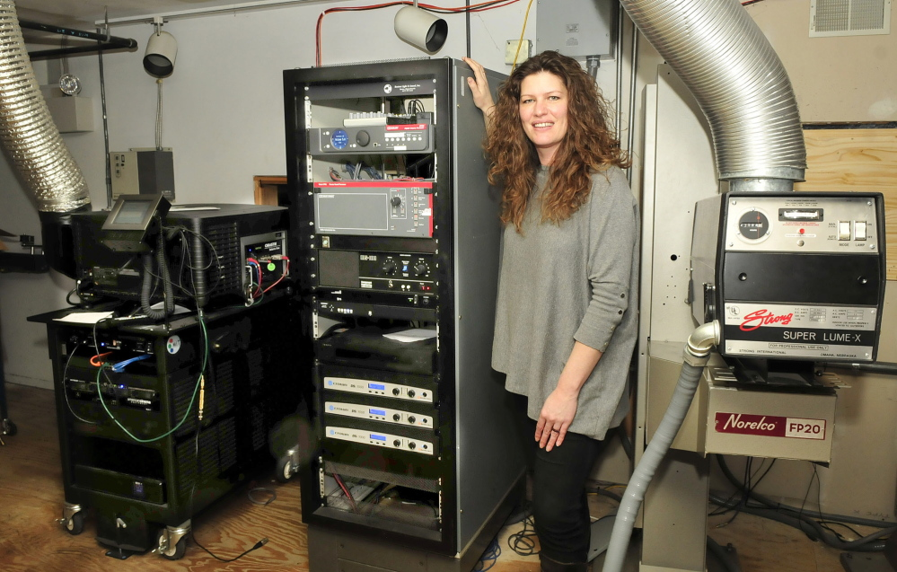 ACTION: Shannon Haines, executive director of the Maine Film Center, stands between digital and film projectors at the Railroad Square Cinema, which is the center of the Maine International Film Festival in July. .