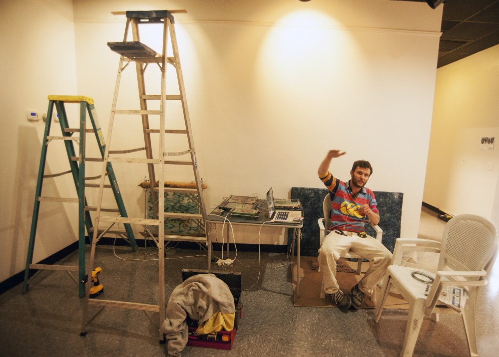 MIFF: Local artist Thom Klepach prepares a work of art to be hung on the new walls of the lobby at Railroad Square Cinemas in Waterville last month. The cinema is the center of the Maine International Film Festival, which is in July.