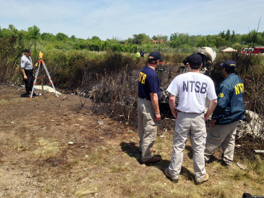 This photo provided by the National Transportation Safety Board, shows NTSB investigators at the scene of a plane that plunged down an embankment and erupted in flames during a takeoff attempt Saturday night at Hanscom Field in Bedford, Mass.