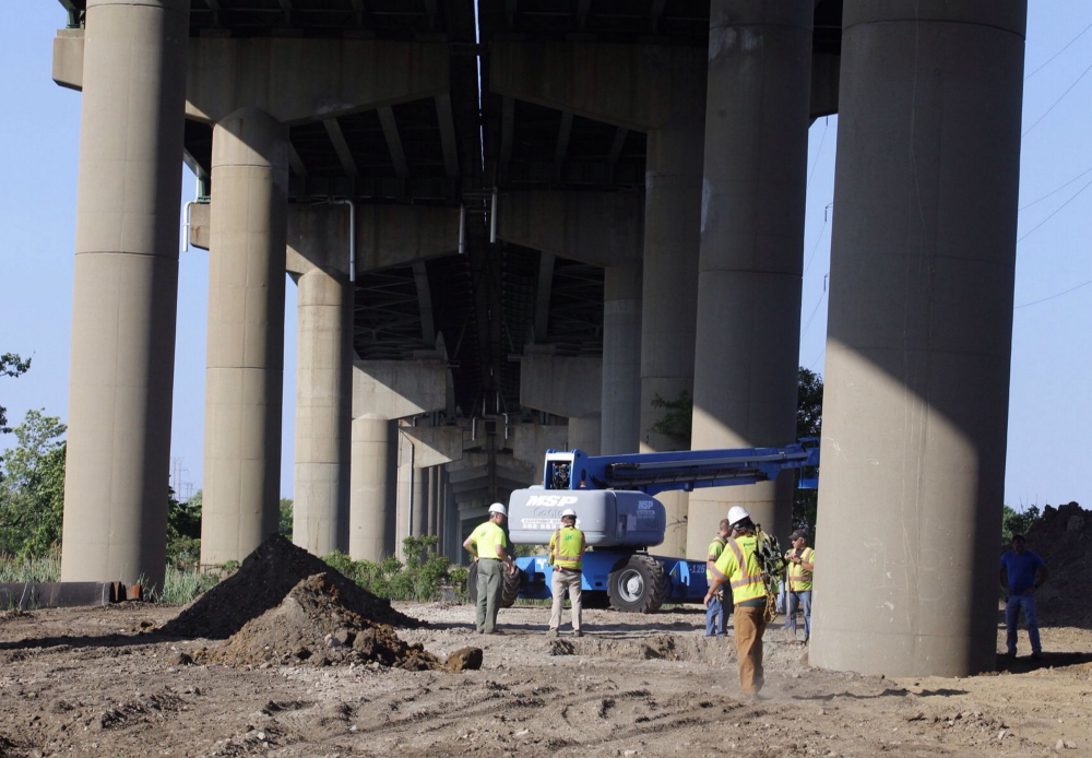 DelDot crew members surround a tilted column supporting a span of the I-495 bridge over the Christina River on Monday. The 4,800-foot bridge normally carries about 90,000 vehicles a day on I-495, which diverts traffic around the city of Wilmington.