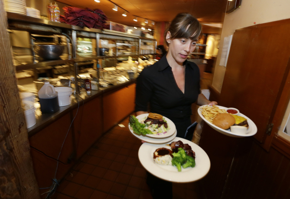 Wendy Harrison, a waitress at the icon Grill in Seattle, works during lunchtime. An Associated Press comparison of the cost of living at several other major U.S. cities found that a $15 minimum wage, like that adopted by Seattle this week, will make a difference, but won't buy a lavish lifestyle.