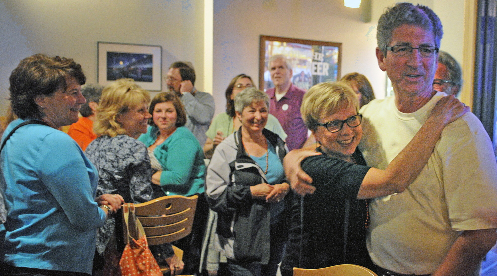 Staff Photo by Andy Molloy LIBRARY CELEBRATION: Betsy Pohl, director at Lithgow Public Library, hugs Augusta Mayor William Stokes Tuesday after they learned voters approved renovations for the Library during a gathering in Augusta.