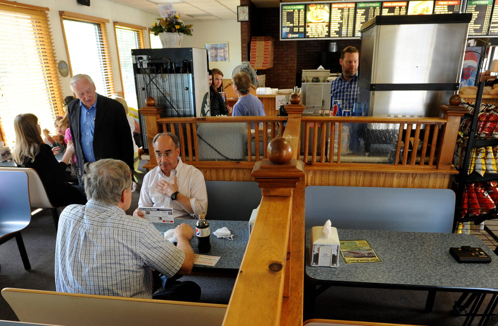 Campaign stop: Bruce Poliquin, left facing, Republican candidate for Maine's 2nd Congressional District, speaks with the public during a visit to the Oakland House of Pizza, in Oakland, on Wednesday.