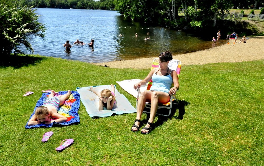 Madison and Izzy Drake and Tracy Liberty relax at the Oakland beach and boat launch on Messalonskee Lake Monday, with no Canada geese in sight. The town had the geese removed by the USDA.