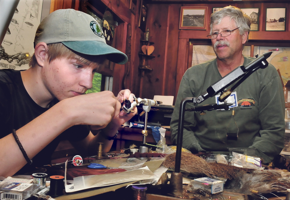 Teenager Sam Kenney works on tying a fly as Jim Dunbar of Winslow watches during a Maine Trout Unlimited Trout Camp in Solon on Thursday.