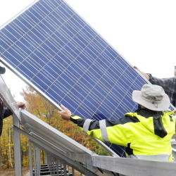 In this October 2014 file photo, workers install a solar electric panel in a ground-mounted solar array for Mt. Abram ski resort, similar to the ground-mounted solar array that is planned for a community solar farm in Wayne.