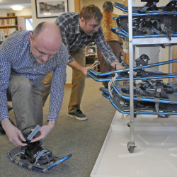 Bailey Library Director Richard Fortin, right, stacks snowshoes Wednesday as Adult Services Librarian Shane Billings learns how to lace a pair from volunteer Margy Burns Knight in Winthrop. The snowshoes, purchased through a donation, are available for check out.