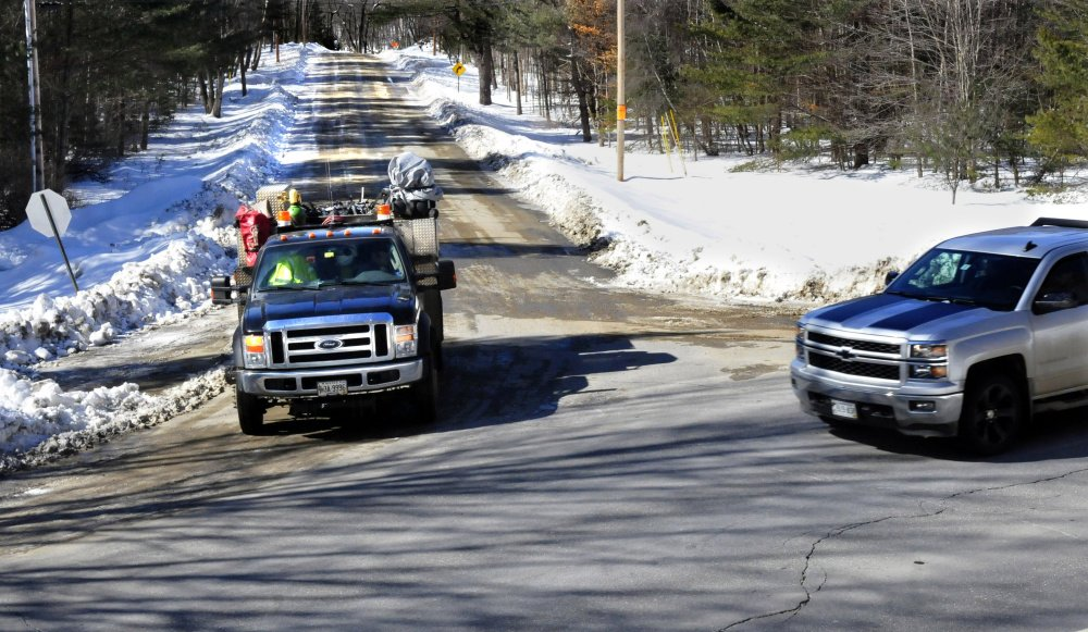 The truck at left stops at the end of the Katie Crotch Road in Embden, which is missing its sign, for another truck passing at the intersection of Route 16 on Thursday. Voters at the Embden town meeting will vote on whether to rename the road to the Cadie Road in hopes of ending the chronic theft of road signs, which costs the town several hundred dollars a year. Town Meeting voters in 2012 rejected a similar proposed change.