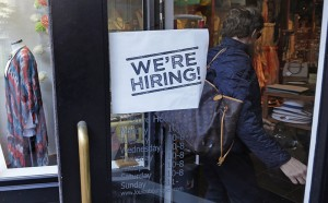 "In this Wednesday, May 18, 2016, photo, a woman passes a ""We're Hiring!"" sign while entering a clothing store in the Downtown Crossing of Boston. On Thursday, May 26, 2016, the Labor Department reports on the number of people who applied for unemployment benefits the week before. (AP Photo/Charles Krupa)"