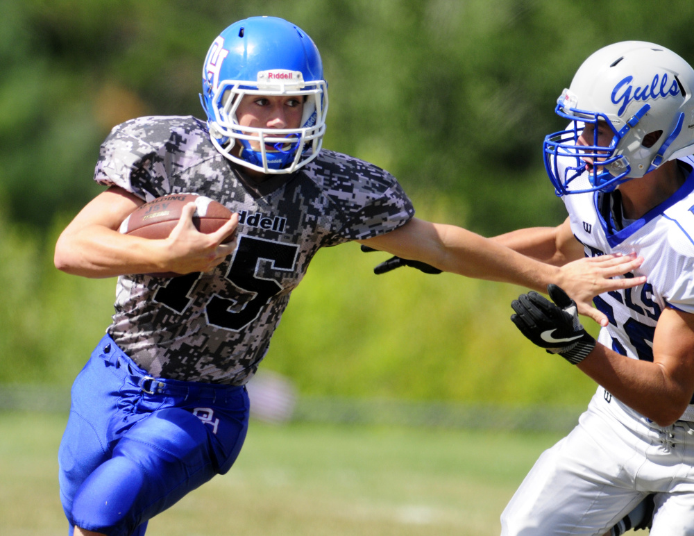 Oak Hill's Steve Gilbert (15) runs around Old Orchard Beach's Mike McCrea during a game on Saturday in Wales.
