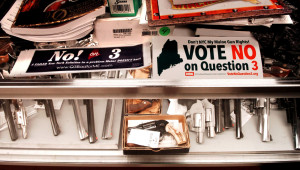 Two signs urging voters to reject Question 3 on the November ballot cover a display case full of handguns at Jim's Gun Shop in Winslow on Monday.