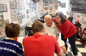 Democrat Emily Cain gives supporter David McVety, of Otisfield, a hug at Daddy O's Diner on Route 26 in Oxford while campaigning Aug. 26 in Oxford County. McVety's wife, Linda, and son Rob watch the encounter.