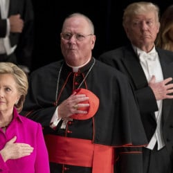 From left, Hillary Clinton, Cardinal Timothy Dolan, Donald Trump and his wife, Melania Trump, stand for the national anthem at a charity gala Thursday.