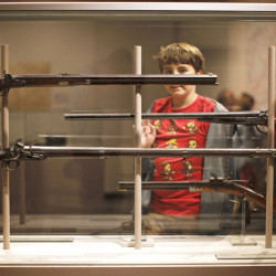 Bodhi Smith of Farmingdale, on a field trip to the Maine State Museum in Augusta, surveys a display of antique rifles produced by Maine gunsmiths in the 1800s.