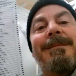 Bill Phillips of Nashua, N.H., takes a selfie with his marked ballot during the New Hampshire primary election last February.