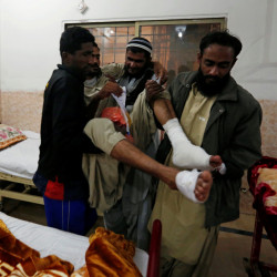 Family members carry a police cadet who was injured in the attack on the Police Training College in Quetta, Pakistan, on Tuesday. A Taliban splinter group and an Islamic State group affiliate both claimed responsibility for the attack.