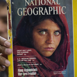 Book shop owner Inam Khan shows the photograph of Afghan refugee Sharbat Gulla in Pakistan on Wednesday. A Pakistani investigator says Gulla had a fake Pakistani identity card.