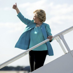 Democratic presidential candidate Hillary Clinton gives a thumbs people who cheer for her as she boards her campaign plane at Tampa International Airport in Tampa, Wednesday, Oct. 26, 2016. (AP Photo/Andrew Harnik)