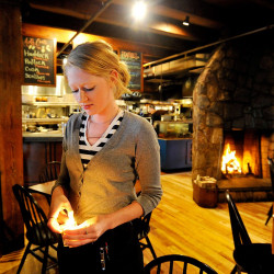 """Desiree Cofran lights candles for tables before dinner Wednesday at Boone's Fish House & Oyster Room in Portland. She says she would quit if her employer eliminated tipping. """"It would be a huge pay cut for me."""" Shawn Patrick Ouellette/Staff Photographer"""