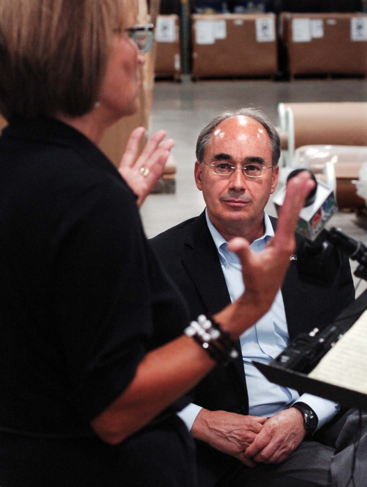 U.S. Rep. Bruce Poliquin, R-2nd District, listens as Auburn Manufacturing President and CEO Kathie Leonard speaks about fair trade practices at the Auburn company on Aug. 30.