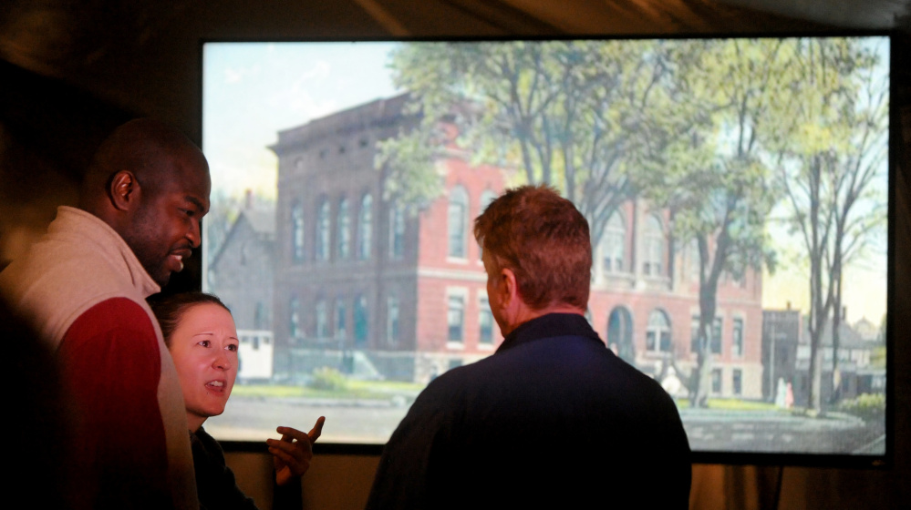 Phil Bofia, left, and Erica Beaster, left center, speak with Dale Foster as historical images flash on a large flat screen in the background Tuesday during Harvest on the Square on Common Street in downtown Waterville. Colby College and the Harold Alfond Foundation matched donations for a total of $20 million for downtown investments.