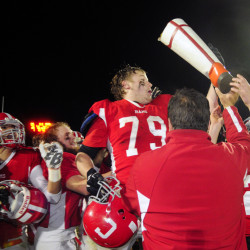 Members of the Cony football team get their hands on the boot after they defeated Gardiner 40-0 in the 138th meeting between the teams last season.