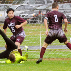Erskine keeper David McGraw flips after making a save but MCI's Devon Varney (8) scores the game-winning goal in the second overtime of a Class B North preliminary game Saturday in South China. MCI's JunSu Jang (35) looks on.