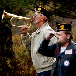 During the dedication of the Canaan Veterans Memorial, Phil Daigle prepares to play taps as Leroy Welch salutes during the ceremony on Sunday.