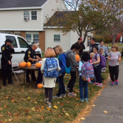 Sgts. Scott Taylor, Laura Drouin and Christian Behr collect Operation Pumpkin contest drawings from school-age children on Glenridge Drive in Augusta. In return each child received a pumpkin.