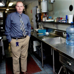 Benton Elementary School Principal Brian Wedge stands on Tuesday beside the school cafeteria kitchen sink, where high levels of lead were detected last week.